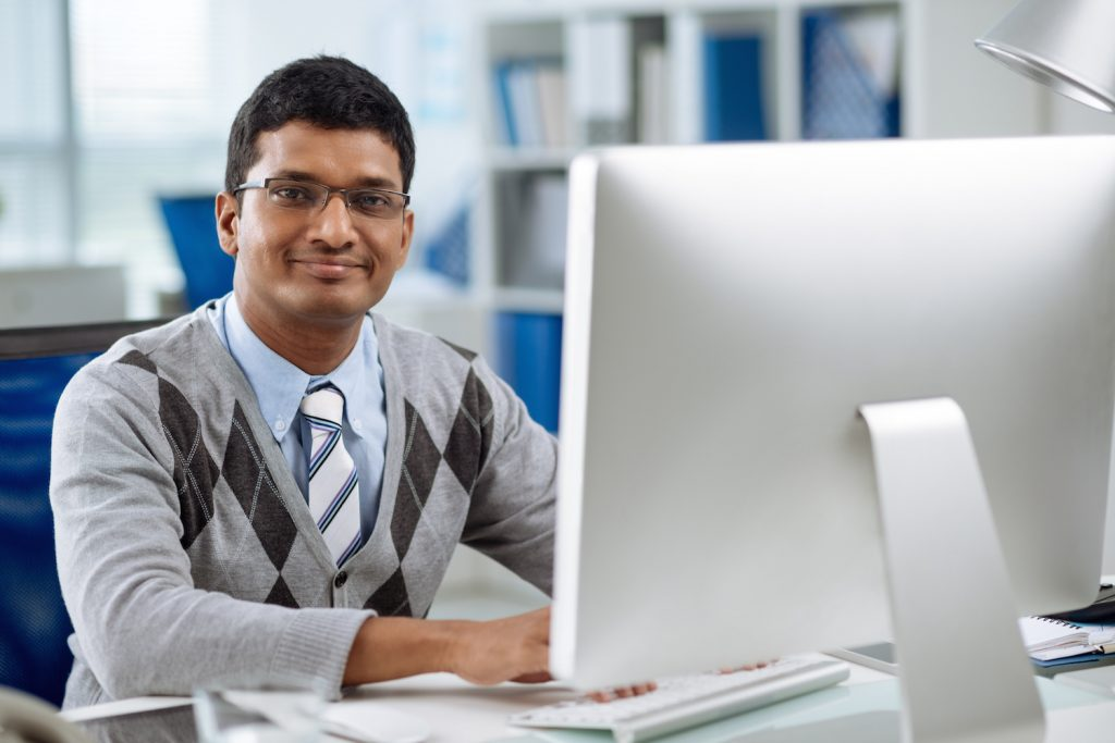 Smiling young software developer working on computer